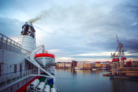 Panoramic view from cruise liner with suspended rescue boat to cargo port with containers and cranes and quay of Helsinki at sunrise, Finland Banque d'images - 109401771