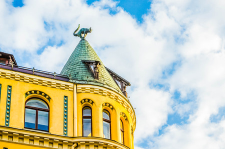 Cat House (KaÄ·u nams) for two cat sculptures, with arched backs and raised tails, on its roof building in old town of Riga, Latvia.