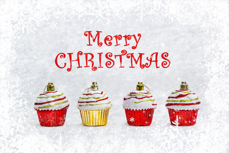 Red and gold Christmas cupcakes - New Year bauble on light snow, winter with snowflakes background with copy space. Concept holidays symbol for Merry Christmas greeting card. Stock Photo