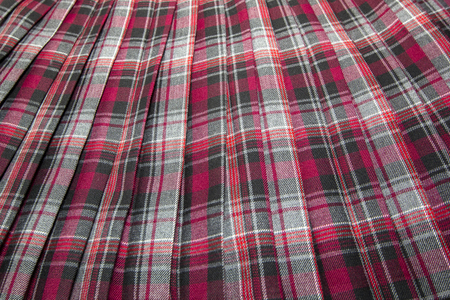 Detail of new fashion plaid pleated skirt: red, maroon, gray tartan school uniform fabric cotton/woolen material, blurred focus