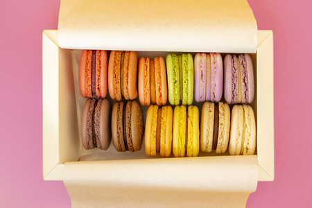 Cake french macaroons, sweet colorful macarons in white box on pink background Standard-Bild