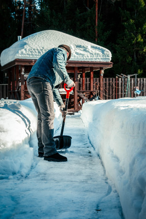Man with shovel removing snow from sidewalk after snowstorm. Winter time in outdoors, clearing snow from backyard.
