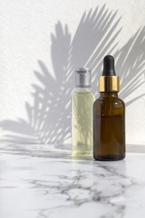 Cosmetic skincare products on marble background with palm leaves shadow. Glass bottle of natural oil, modern concept of organic beauty trend skin care