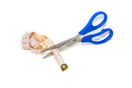 Scissors cutting measuring tape over white background. Work lifestyle concept. Body care.