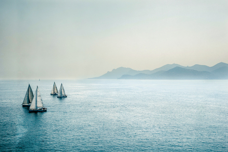 Sailing regatta or a group of small water racing boats in the Mediterranean, a panoramic view of the blue mountains on a horizon