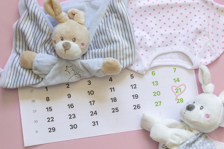 Set of newborn accessories in anticipation of  child - calendar with circled number 21 (twenty one), baby clothes, toys on pink background. Copy space, flat lay, top view.