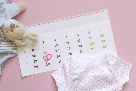 Set of newborn accessories in anticipation of child - calendar with circled number 23 (twenty three), baby clothes, toys on pink background. Flat lay, top view.