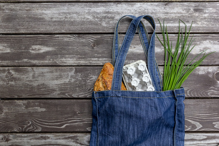 Fresh produce in blue denim market bag on wooden background, flat lay. Eco friendly reusable shopping bag for minimize waste, Earth Day, no plastic. Stock Photo