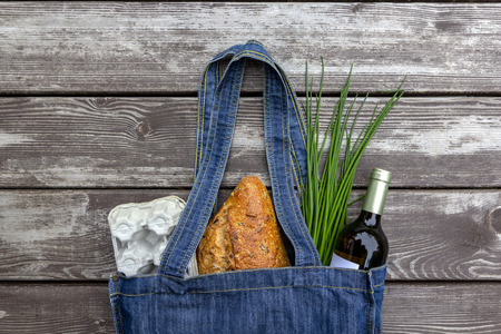 Fresh produce in blue denim market bag on wooden background, flat lay. Eco friendly reusable shopping bag for minimize waste, Earth Day, no plastic. Stok Fotoğraf