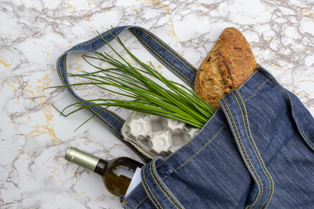 Fresh produce in blue denim market bag on marble kitchen table background, flat lay. Eco friendly reusable shopping bag for minimize waste, Earth Day, no plastic. Stock Photo