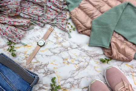 Fashion womens clothes, tropical leaves trendy accessories set on beige white marble background. Stylish casual outfit. Vanilla pastel colors. Flat lay, top view