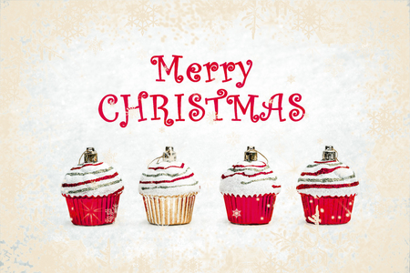 New Year greeting card - Christmas bauble cupcakes on white snow with snowflakes background. Russian translation: Happy New Year.
