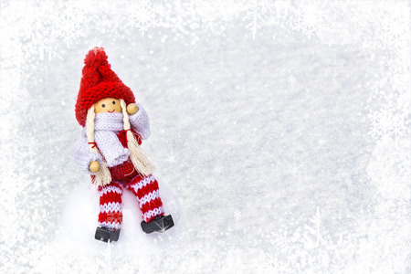 Christmas bauble girl in knitted clothes and red Santa Claus hat on light snow, winter with snowflakes background with copy space. Concept holidays symbol for Merry Christmas, New Year Stock Photo