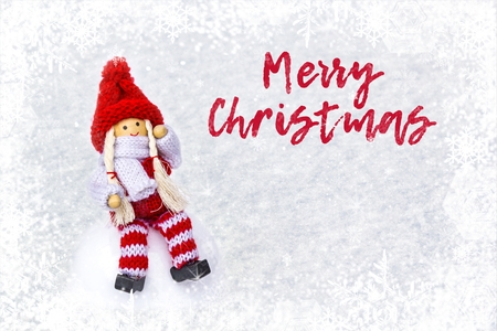 Christmas bauble girl in knitted clothes and red Santa Claus hat on light snow, winter with snowflakes background with copy space. Words Merry Christmas for greeting card- concept holidays New Year Stok Fotoğraf