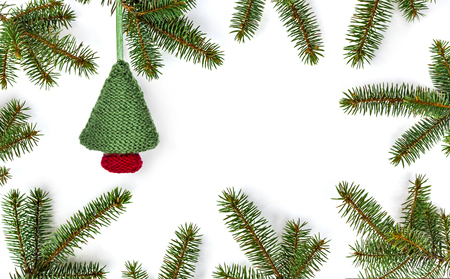 Knitted Christmas bauble, Christmas tree in frame of green fir branches on white background - winter composition, new year  background. Flat lay, top view with copy space.