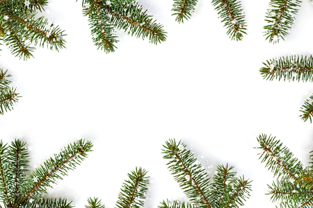 Frame of green fir branches on white background - christmas composition, new year winter background. Flat lay, top view with copy space.