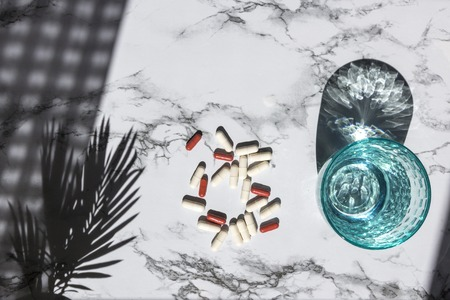 Blue glass of clean water and pills on white marble background with shadows from sunlight. Concept for pharmacy, medical dietic supplements Stok Fotoğraf