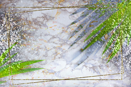 Gold frame, green tropical palm leaves on marble background with gold silver sparkles. Flat lay, top view, copy space