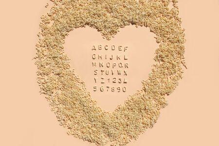 Letters of alphabet of pasta for kids food on light pink background. Pastel color for childrens meals. Stok Fotoğraf