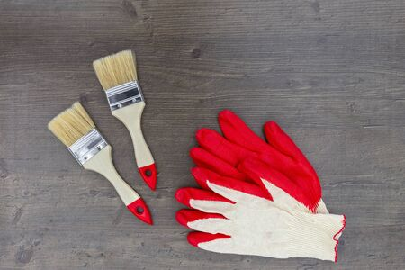 Paint brushes for repair and work gloves red on wooden background. Top view, flat lay
