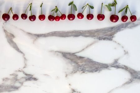 Colourful fresh bright pattern with ripe red cherry and leaf on marble table. Top view, flat lay
