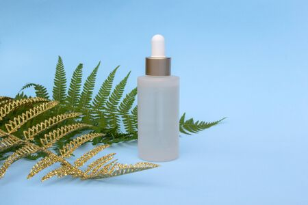 Glass bottle of natural oil on light blue background with green, golden fern palm leaves. Cosmetic skincare products, modern concept of organic beauty trend.