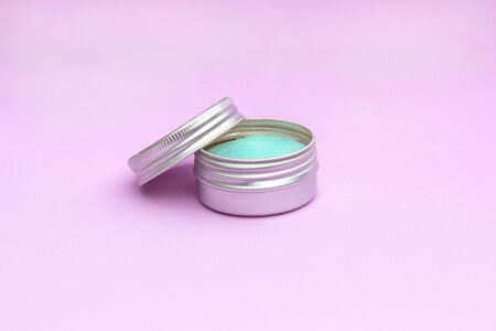 Blank silver cream jar on light pink background. Cosmetic skincare products, modern concept of organic beauty trend.