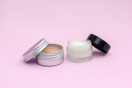 Blank silver and glass cream jar on light pink background. Cosmetic skincare products, modern concept of organic beauty trend.