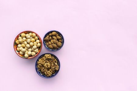 Assortment  mix of nuts, hazelnuts, almonds, walnuts in bowls on pink background. Flat lay, top view, copy space 版權商用圖片