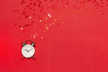 Time for love - silver alarm clock with red hearts on red background. Copy space, top view, flat lay