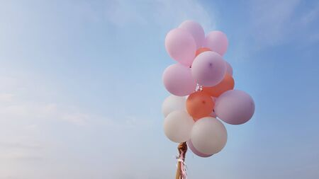 Flying balloons of delicate pink and white coral flowers in female hand on background of blue sky with clouds Foto de archivo