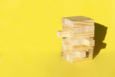 Wood jenga game with wooden block Stack tower on yellow background, manage risk and strategy.