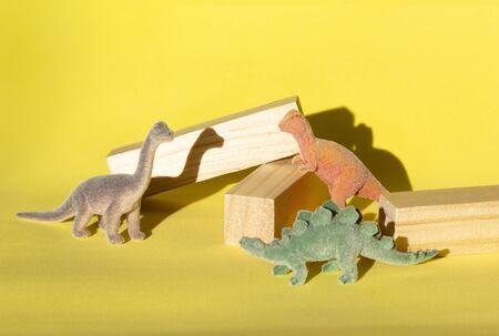 Colored toy dinosaurs (Brachiosaurus, Stegosaurus, Tyrannosaurus) with wooden beams on yellow background 版權商用圖片