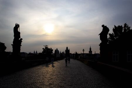 Silhouettes Charles Bridge, Old Town Tower, statues and happy tourists at sunrise, Prague, Czech Republic
