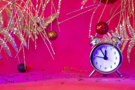 Christmas or New Year composition with alarm clock and beautiful gold decorations on red neon background, Xmas countdown Stock fotó