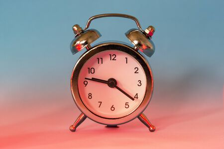 Silver shiny alarm clock in retro vintage style on blue red neon background. Minimal modern style. Stock fotó