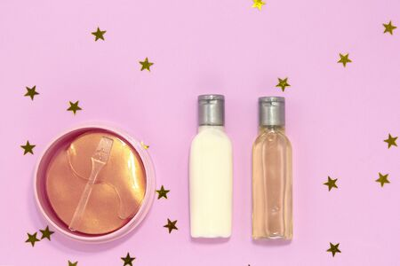 Set of decorative beauty accessories for woman - hydrogel cosmetic eye patch, jars and bottles with cream and gel for skin care on pink background with golden stars. Flat lay, top view Stock fotó - 131332208