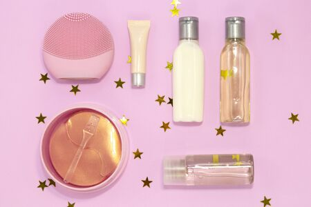 Set of decorative beauty accessories for woman - silicone facial cleansing brush, hydrogel cosmetic eye patch, jars and bottles with cream and gel on pink background with golden stars. Flat lay, top view Stock fotó - 131332369