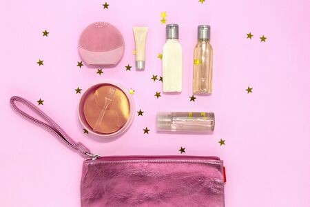 Cosmetic bag with makeup products - silicone facial cleansing brush, hydrogel eye patch, jars and bottles with cream and gel on pink background with golden stars. Flat lay, top view