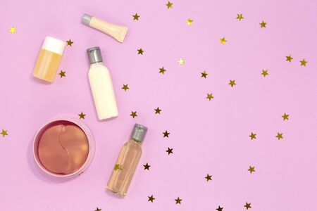 Set of decorative beauty accessories for woman - hydrogel cosmetic eye patch, jars and bottles with cream and gel for skin care on pink background with golden stars. Flat lay, top view Stock fotó