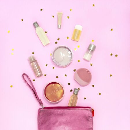 Cosmetic bag with makeup products - cream jars, gel bottles, silicone facial cleansing brush, hydrogel eye patch, on pink background with golden stars. Flat lay, top view