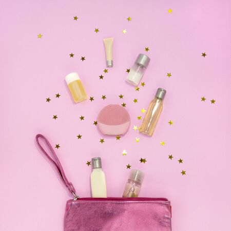 Cosmetic bag with makeup products - cream jars, gel bottles, silicone facial cleansing brush on pink background with golden stars. Flat lay, top view
