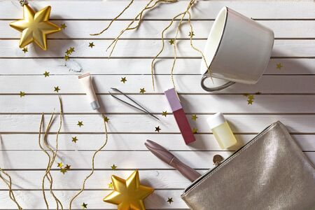 New Years set of womens makeup cosmetics. Women accessories in silver cosmetic bag - mascara, creams, lotions, lipstick and cup on Christmas white wooden background with golden stars. Stock fotó