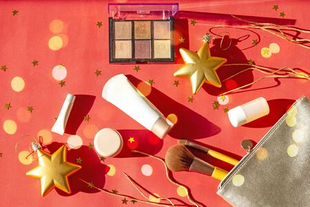 Christmas composition of womens accessories - silver cosmetic bag with makeup, eyeshadows, face brushes, creams and lotions on red New Year background with lights and gold stars. Flat lay, top view