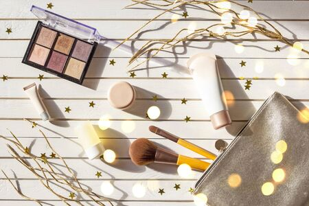 Christmas composition of womens accessories - silver cosmetic bag with makeup, eyeshadows, face brushes, creams and lotions on New Year background with lights and gold stars. Flat lay, top view