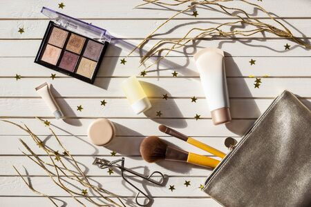 New Years set of girl makeup cosmetics. Women accessories in silver cosmetic bag -  eyeshadows, face brushes, creams and lotions on Christmas white wooden background with golden stars.