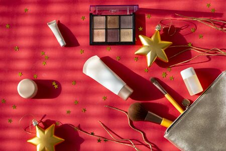 New Years set of girl makeup cosmetics. Women accessories in silver cosmetic bag -  eyeshadows, face brushes, creams and lotions on red Christmas background with golden stars.