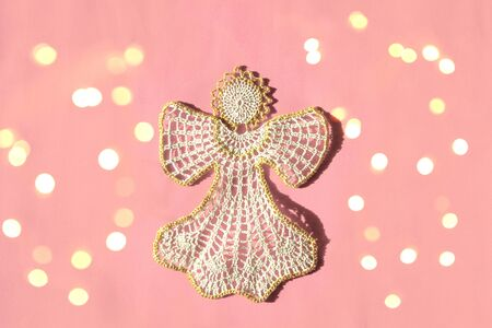 Christmas angel knitted bauble on pink New Year background with bright lights, flat lay, top view