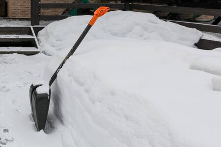 Shovel for cleaning remove tracks from snow in country house in winter. Stock fotó