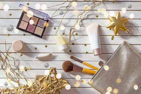 Christmas composition of womens accessories - silver cosmetic bag with makeup, eyeshadows, face brushes, creams and lotions on New Year background with gold stars. Flat lay, top view